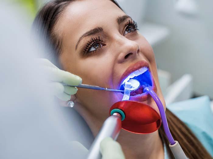 Mulher fazendo clareamento dental a laser