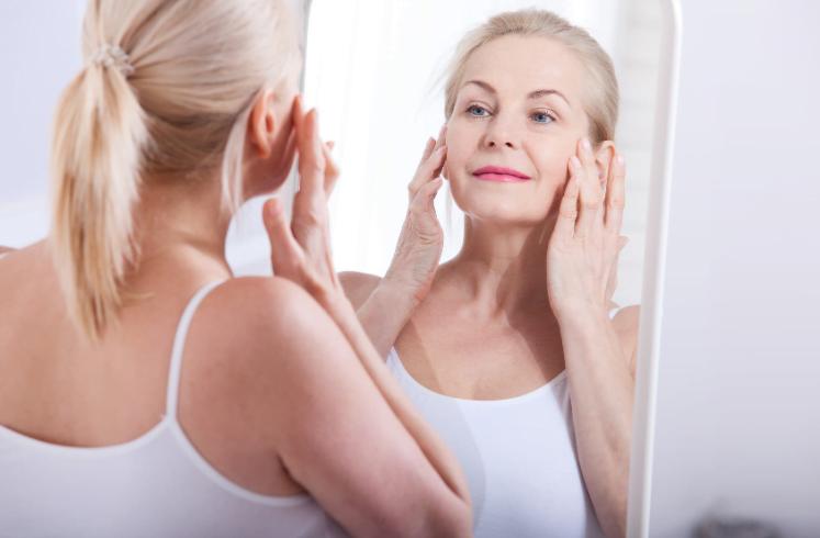 Mulher no espelho após preenchimento de colágeno